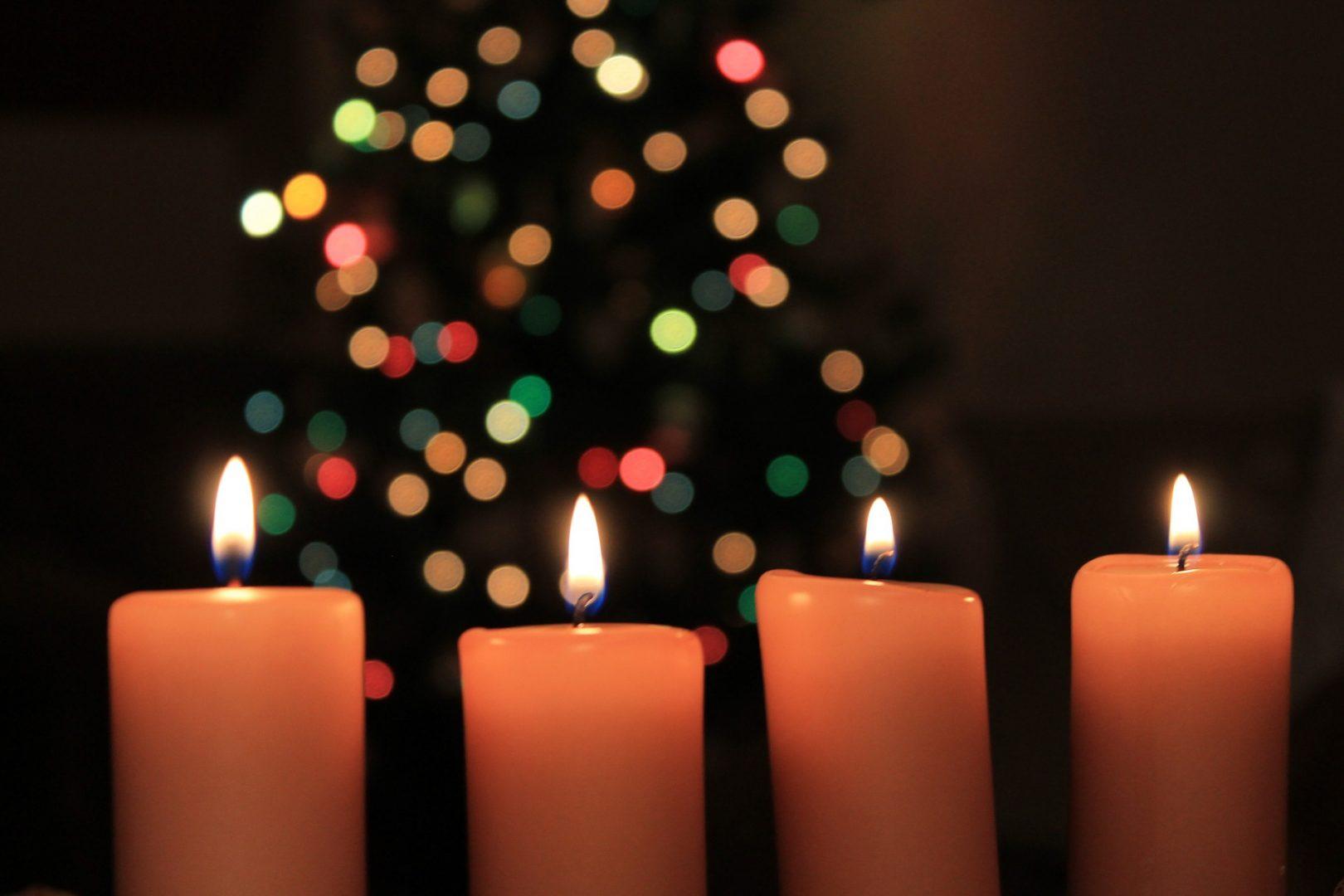Lämna aldrig ljus obevakade. Bilden visar fyra stearinljus i en julmiljö.